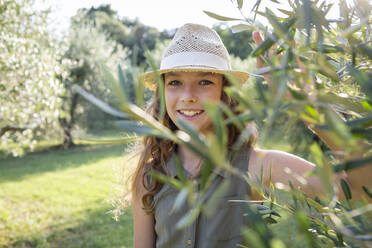 Smiling girl with straw hat standing in an olive grove, Tuscany, Italy - OJF00360
