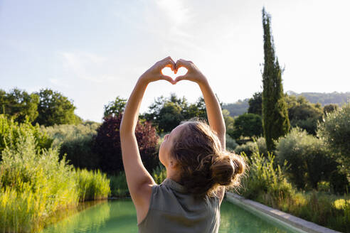 Rear view of a girl standing at swimming pool, forming a heart with her hands - OJF00363