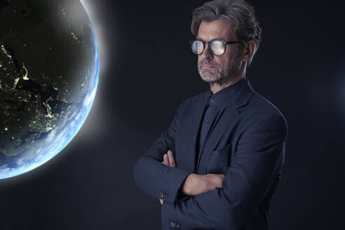 Portrait of mature businessman against dark background watching floating planet earth - PHDF00006