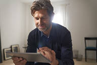 Portrait of smiling mature man using digital tablet at home - PHDF00012