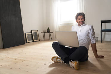 Portrait of smiling mature man with laptop sitting on the floor at home - PHDF00021