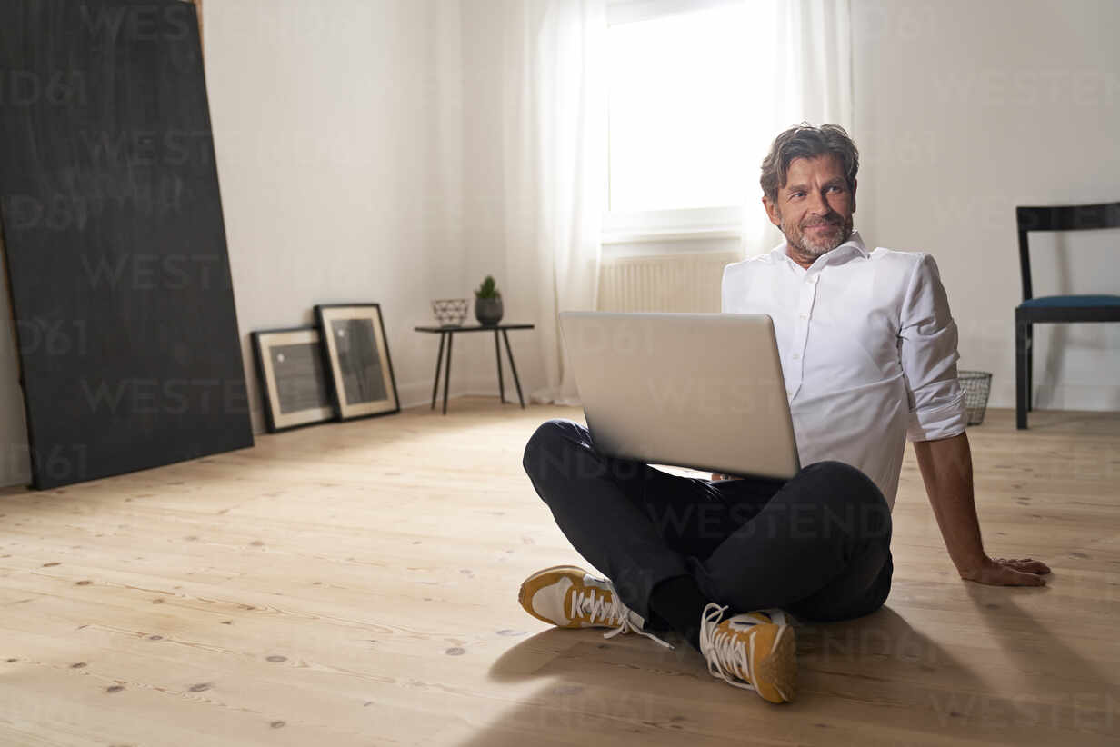 Portrait of smiling mature man with laptop sitting on the floor at home - PHDF00021 - Isabella Bellnini/Westend61