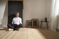 Relaxed mature man with digital tablet sitting on the floor at home looking at distance - PHDF00024