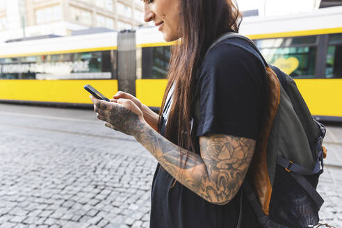 Tattooed young woman with backpack text messaging, Berlin, Germany - WPEF02368