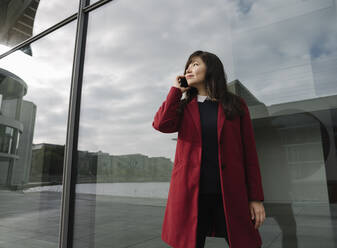 Businesswoman standing near to modern building and using smartphone - AHSF01519