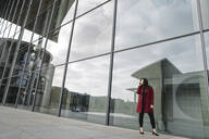 Businesswoman standing near to modern building and using smartphone - AHSF01522