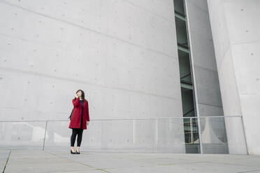 Businesswoman standing near to modern building and using smartphone - AHSF01525
