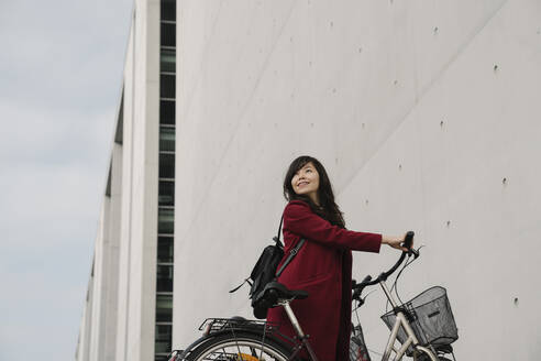 Businesswoman taking bicycle in the background of modern building - AHSF01528