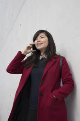 Portrait of modern businesswoman using smartphone in front of a wall - AHSF01534