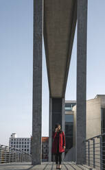 Businesswoman walking on a bridge and using smartphone - AHSF01540