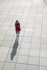 View from above of walking modern businesswoman standing on concrete floor - AHSF01543
