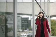 Businesswoman walking near to modern building and using smartphone - AHSF01549