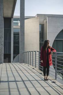 Modern businesswoman standing on a bridge and looking sideways, Berlin, Germany - AHSF01552