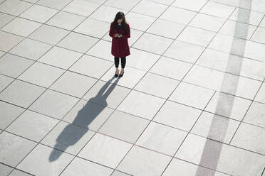 Businesswoman using smartphone and standing on concrete floor - AHSF01555