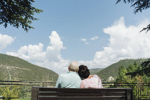 Back view of senior couple sitting on a bench looking at view, Jaca, Spain - AHSF01561