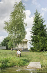 Senior couple relaxing in front of holiday home, Kalvene, Latvia - AHSF01564