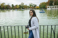 Woman with camera standing at a lake in El Retiro park, Madrid, Spain - KIJF02833