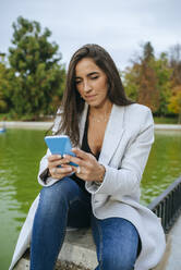 Woman using her smartphone in a park - KIJF02839