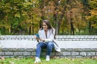 Smiling woman using her smartphone in a park - KIJF02845