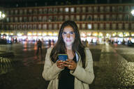 Portrait of a woman using her smartphone on Plaza Mayor at night, Madrid, Spain - KIJF02848