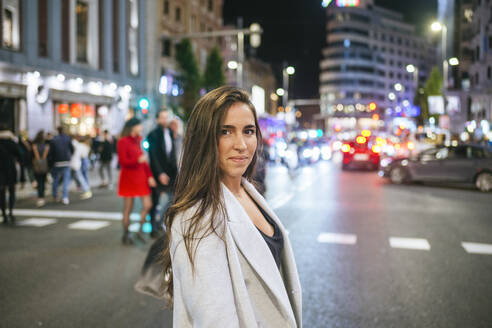 Woman walking on a street in the city at night - KIJF02854