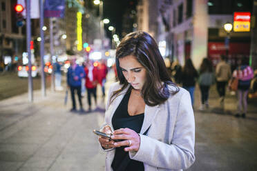 Woman using her smartphone in the street at night - KIJF02857