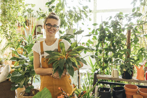 Portrait of a smiling young woman holding a plant in a small gardening shop - VPIF01841