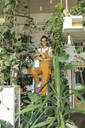 Portrait of a young woman standing on a ladder in a small gardening shop - VPIF01844