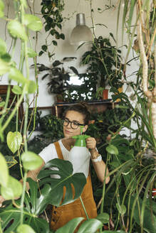 Young woman caring for plants in a small shop - VPIF01847