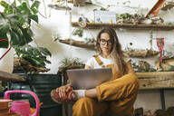 Young woman using laptop in a small gardening shop - VPIF01850