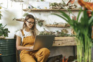 Young woman using laptop in a small gardening shop - VPIF01853
