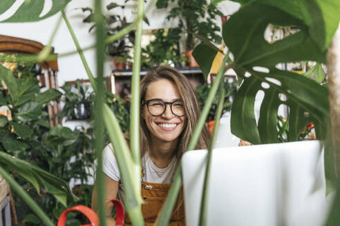 Portraitof a happy young woman with laptop surrounded by plants - VPIF01856