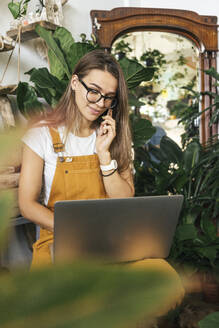 Young woman with laptop on the phone in a small gardening shop - VPIF01859