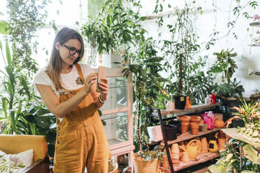 Young woman taking smartphone picture in a small gardening shop - VPIF01868
