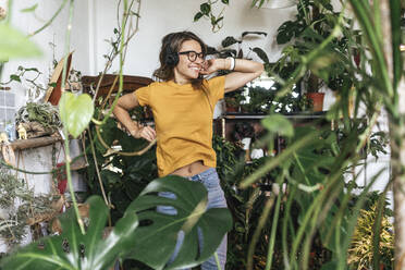 Cheerful young woman surrounded by plants listening to music with headphones - VPIF01877