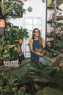 Happy young woman with dinosaur figurine sitting on the floor in a small shop with plants - VPIF01886