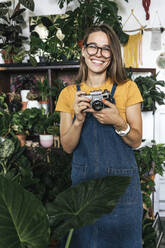 Portrait of a happy young woman with a camera in a small gardening shop - VPIF01889
