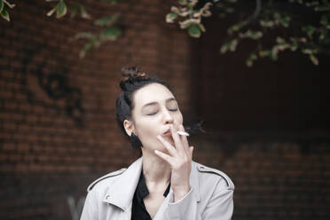 Portrait of woman smoking with eyes closed - EYAF00712