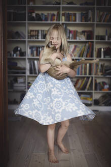 Blond little girl dancing with her Burmese cat at home - EYAF00715
