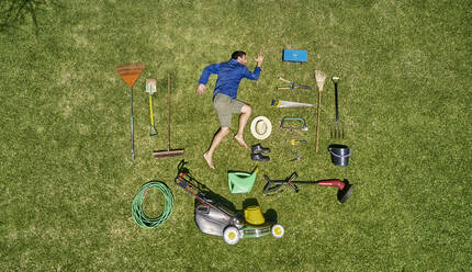 View from above of a gardener in laying on the grass with all the tools he need for take care of garden - VEGF00988