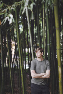Man standing in bamboo forest - EYAF00716