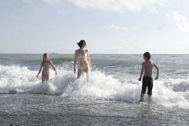 Happy mother with two kids having fun in the sea - EYAF00719