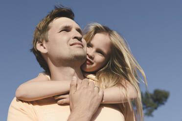 Father carrying his little daughter piggyback under blue sky - EYAF00725
