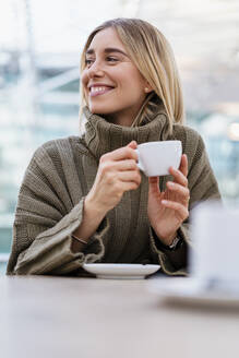 Portrait of a smiling young woman holding cup of coffee looking away - DIGF08974