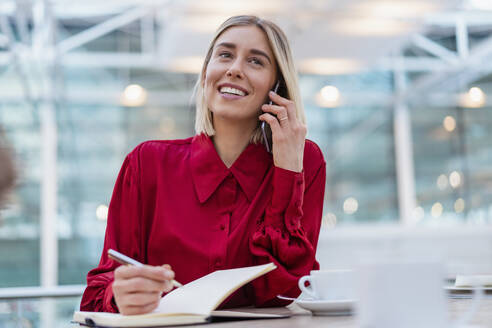 Smiling young businesswoman with notebook on the phone - DIGF08980