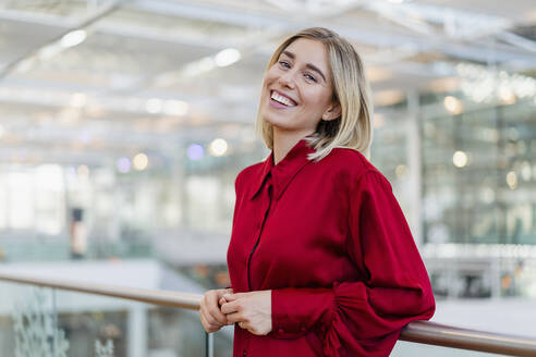 Portrait of a happy young businesswoman standing at a railing - DIGF08989