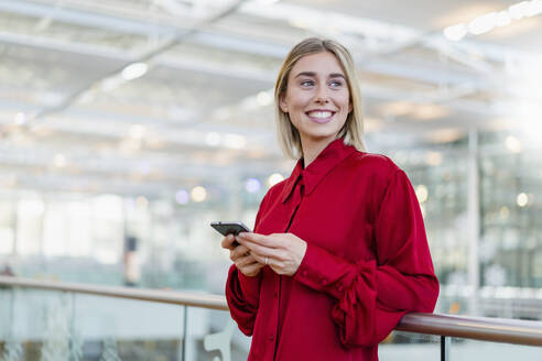 Smiling young businesswoman standing at a railing with cell phone - DIGF08992