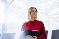 Smiling young businesswoman with folder sitting in waiting area - DIGF09001