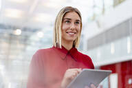 Smiling young businesswoman wearing red shirt using tablet - DIGF09007