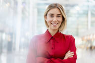 Portrait of a confident young businesswoman wearing red shirt - DIGF09010